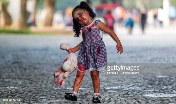 Girl takes part in the annual Zombie Walk in Sao Paulo, Brazil, on November 2, 2018. - Hundreds of people took to the streets in traditional costumes...