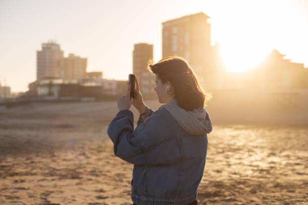 girl takes photos on phone of  sunset on beach of the Atlantic ocean