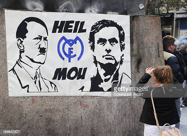 A girl takes pictures of a poster depicting Adolph Hitler and Real Madrid's Portuguese coach Jose Mourinho with the logo of the Real Madrid FC and...