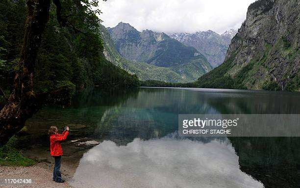 A girl takes pictures of the small Obersee lake near Schoenau southern Germany on June 19 2011 The lake is located in the Berchtesgaden National Park...