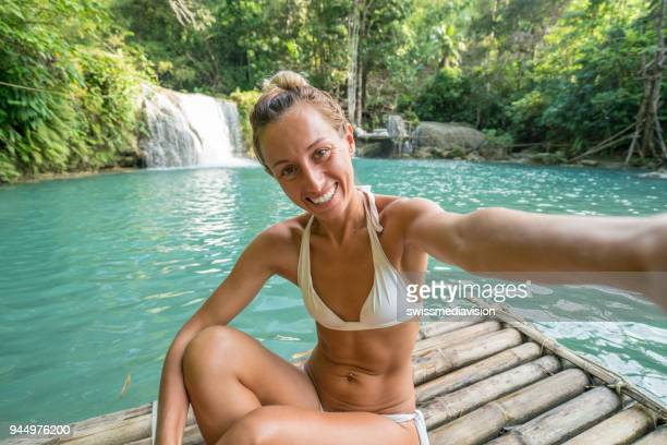 girl takes selfie at beautiful waterfall in tropical rainforest - one young woman only stock pictures, royalty-free photos & images