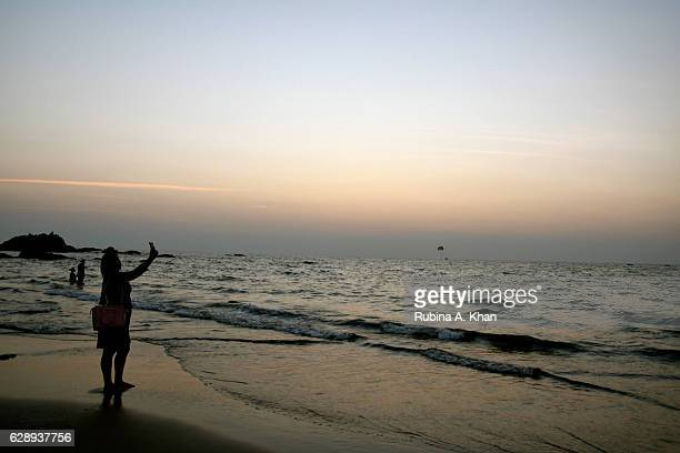 A girl takes selfies as the sun sets on Vagator Beach at W Goa on December 9 2016 in Goa India