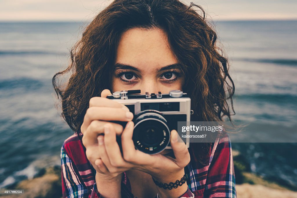 Girl taking a photo at sea with a film camera : Stock Photo