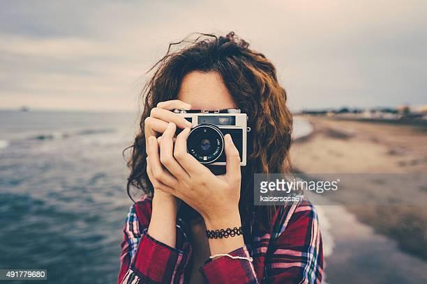 Ragazza fare una foto sul mare con una macchina fotografica di film