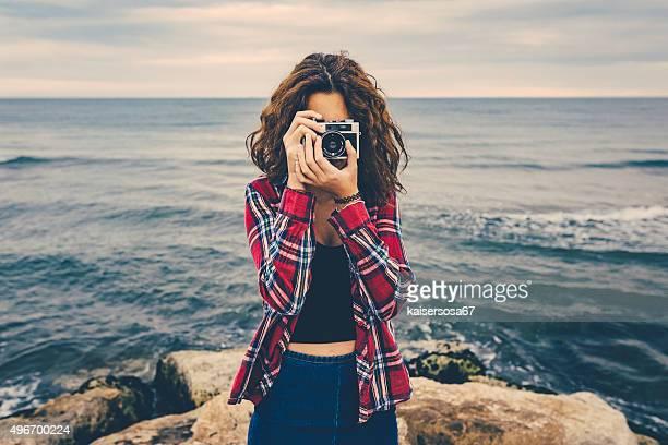 Rapariga a tirar uma foto no mar com uma câmara de filme