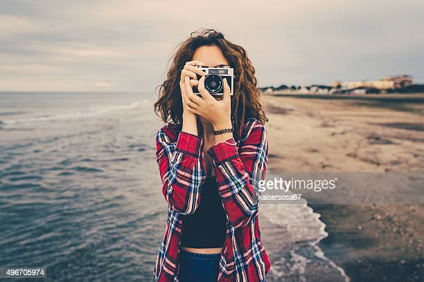 Girl taking a photo at sea with a film camera