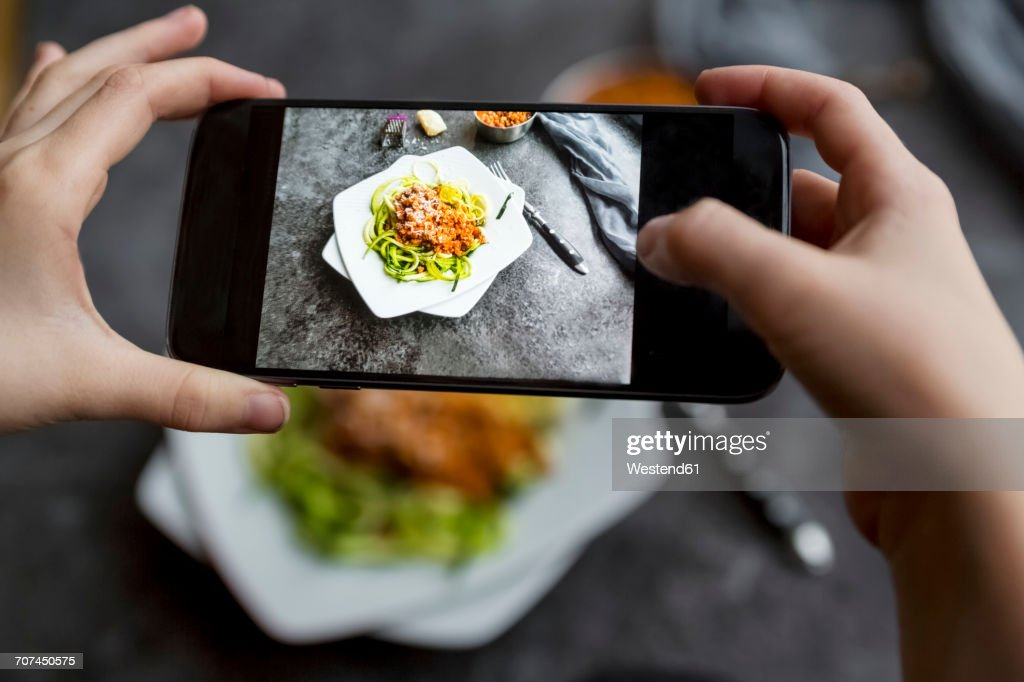 Girl taking a photo zoodles with vegetarian bolognese sauce with her smartphone, close-up : Stock Photo