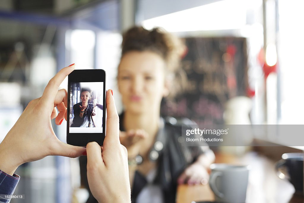 girl taking a photograph of her friend : Foto de stock
