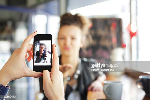 girl taking a photograph of her friend - photo messaging stock pictures, royalty-free photos & images