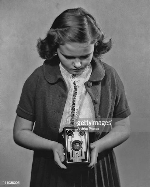 A girl taking a photograph with a Kodak box Brownie camera circa 1935