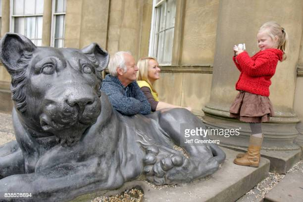 A girl taking a picture of her mother and grandfather posing with a lion statue at Heaton Hall