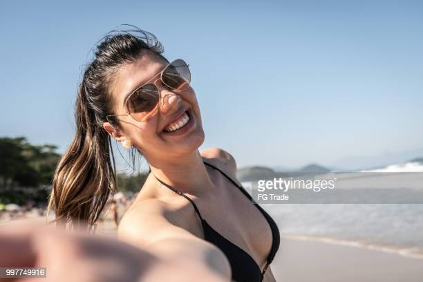 menina tomando um selfie num dia de verão na praia - 25 30 anos - fotografias e filmes do acervo