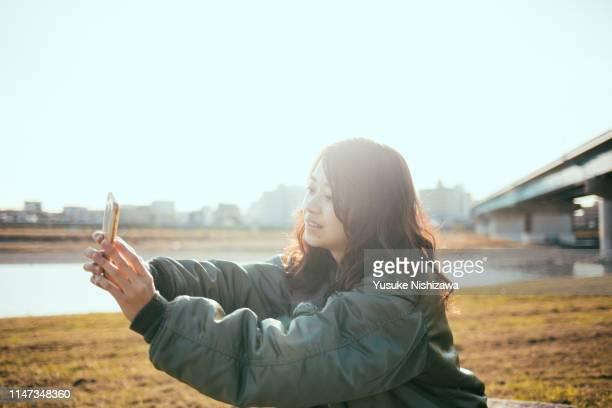 girl taking a selfie with a smartphone - yusuke nishizawa stock-fotos und bilder