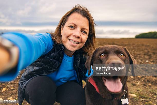 girl taking a selfie with her pet dog - mature women stock pictures, royalty-free photos & images