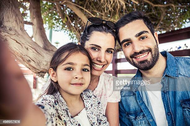 Girl taking a selfie with parents