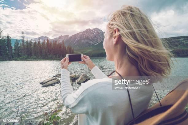 mädchen, die ein smartphone bild berglandschaft - fotohandy stock-fotos und bilder