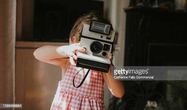 girl taking an image with an instant camera - copy space stock pictures, royalty-free photos & images