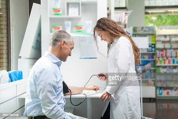 Girl taking blood pressure to mature man
