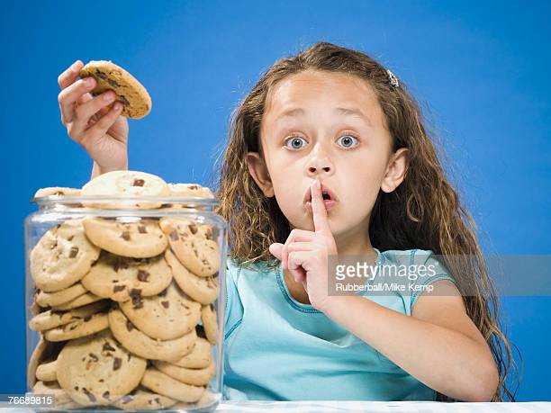 Girl taking chocolate chip cookie from jar and hushing