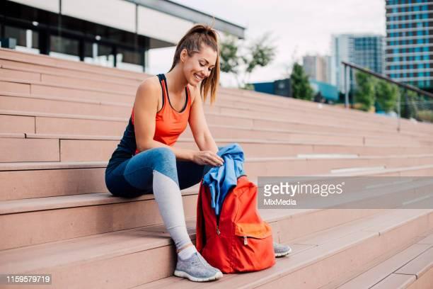 ジムバッグから服を取り出す女の子 - スポーツバッグ ストックフォトと画像