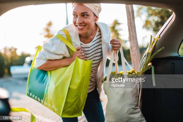 girl taking groceries out of reusable shopping bags - reusable bag stock pictures, royalty-free photos & images