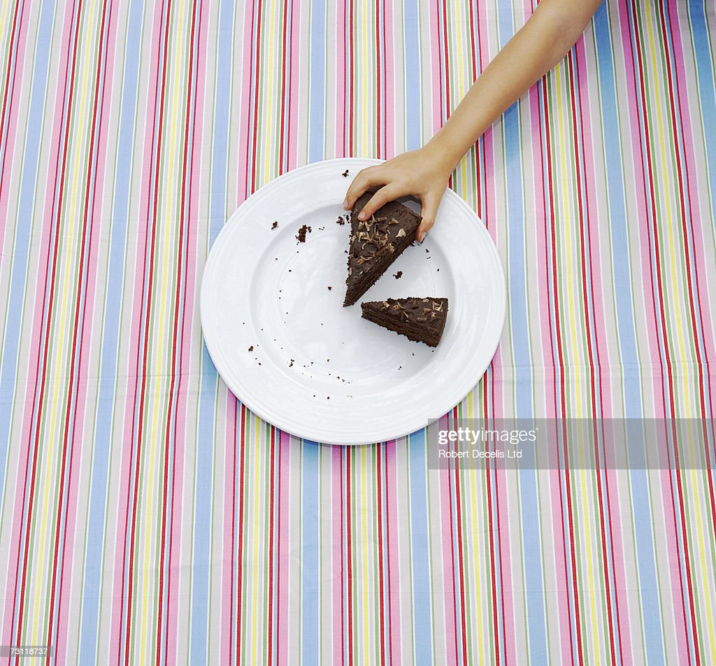 Girl (8-9) taking large slice of cake from plate on table : ストックフォト