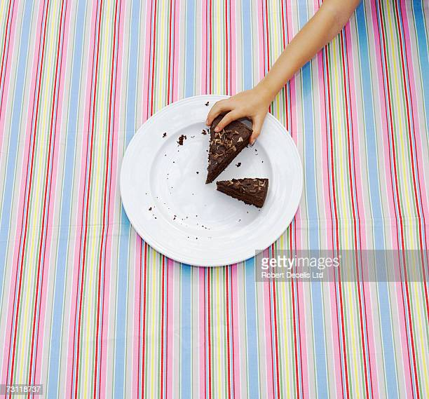Girl (8-9) taking large slice of cake from plate on table