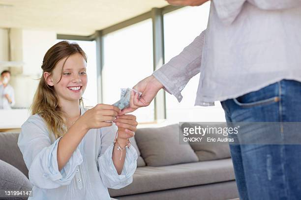 Girl taking paper currency from her mother