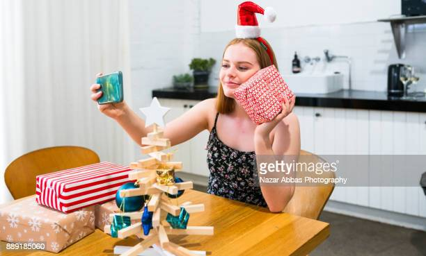Girl taking photo of christmas gifts she got.