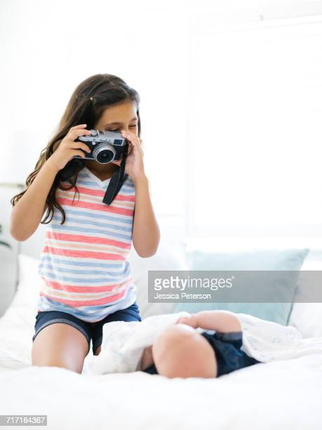 Girl (10-11) taking photo of her small brother (12-17 months) lying on bed