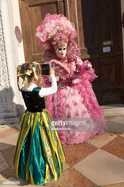 girl taking photo of pink mask, carnival, san zacharias, venice - mardi gras girls stock photos and pictures