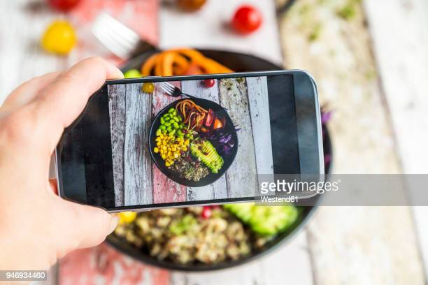 girl taking photo of vegan lunch bowl with cell phone, close-up - fotografie stock-fotos und bilder