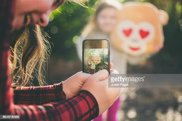 Girl taking photo of younger sister with emoji cushion
