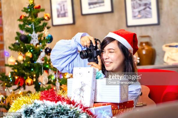 A girl taking photo using digital camera during Christmas gathering with friends