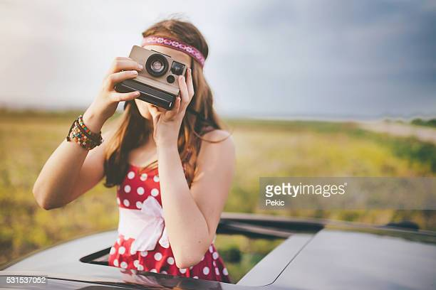 Girl taking photo with instant camera throught car sunroof