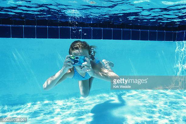 Girl (9-11) taking photograph in swimming pool, underwater view
