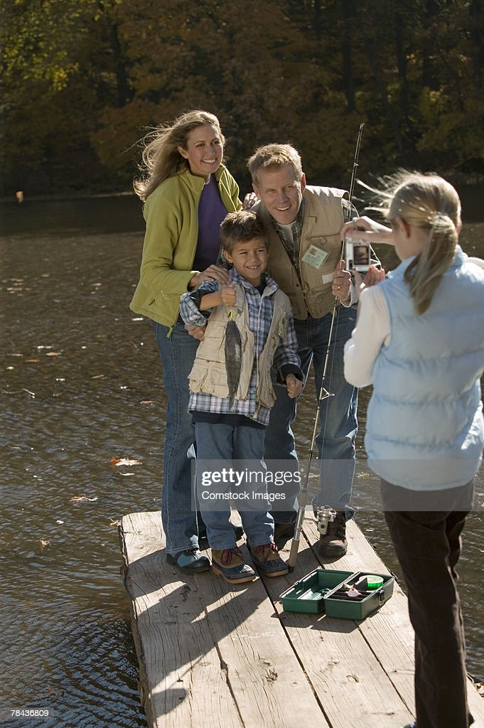 Girl taking photograph of family fishing : Stockfoto