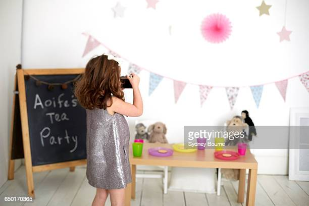 Girl taking photograph of soft toys at tea party