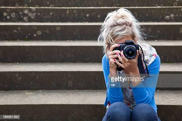 Fotografia de tomar Menina sentada na pedra passos