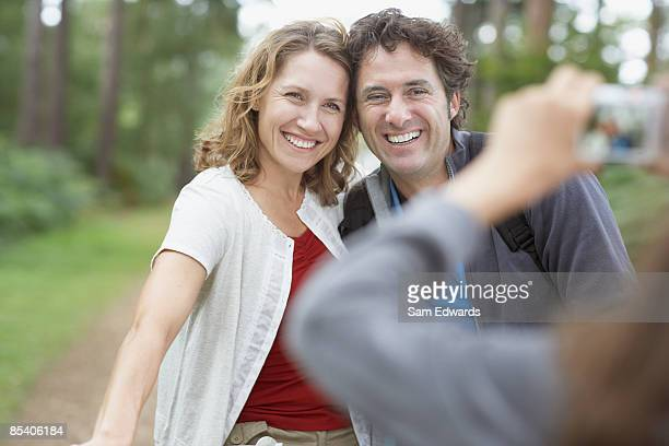 Girl taking photographs of parents in woods