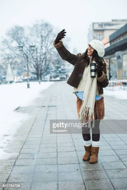 Girl taking photos of herself on city street