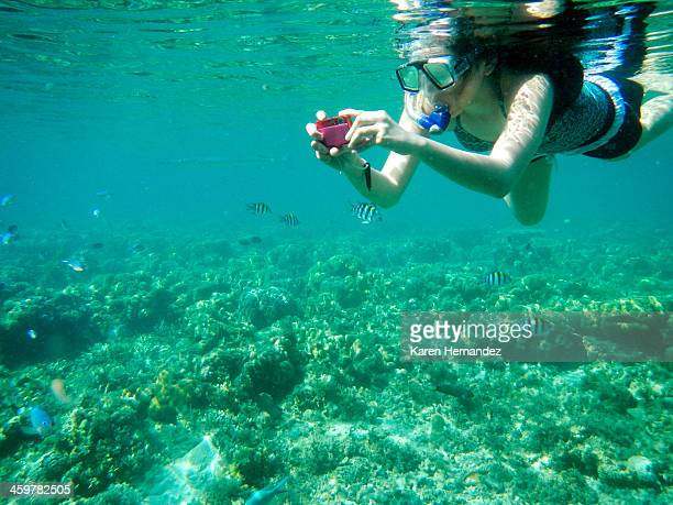 girl taking photos while snorkeling