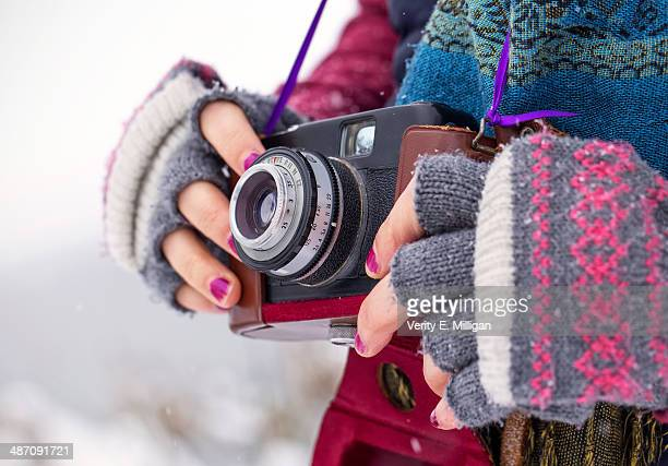 Girl taking photos with vintage camera in snow