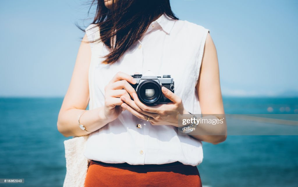 Girl taking photos with vintage film camera in the beach on a sunny day
