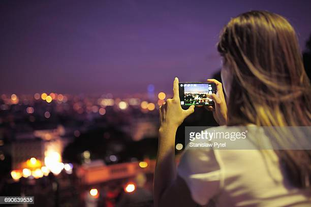 Girl taking picture of city at night