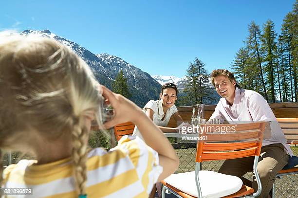 Girl taking picture of parents on panorama terrace in the mountains