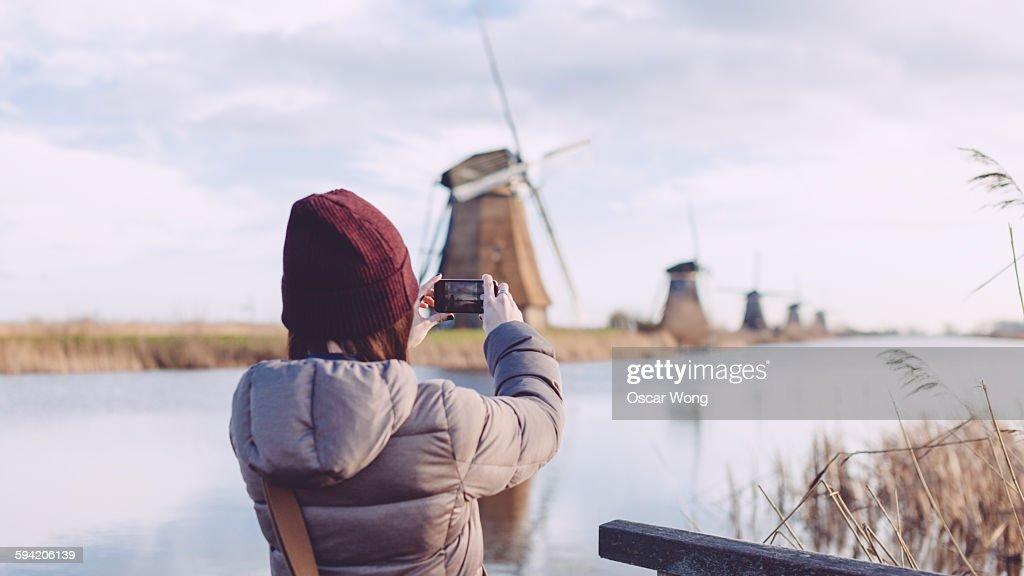 Girl taking picture of windmills with smartphone : Stock Photo