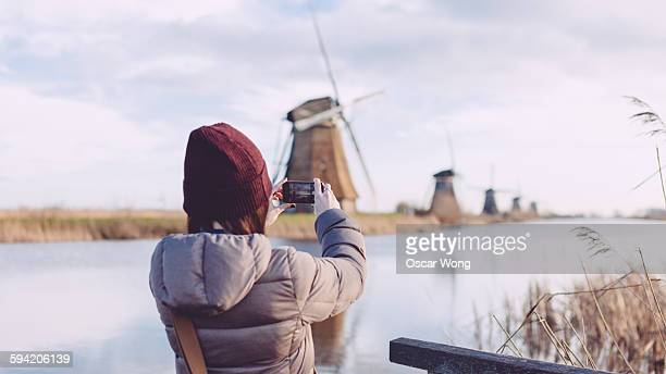 Girl taking picture of windmills with smartphone