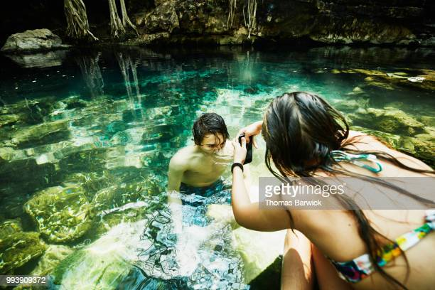 Girl taking picture with smartphone of brother swimming in cenote while on vacation