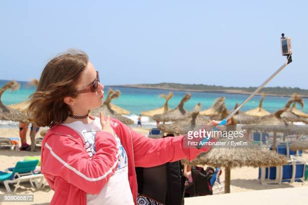 girl taking selfie at beach against clear sky - one girl only stock pictures, royalty-free photos & images